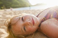 Caucasian girl laying in sand - stock photo