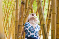 Caucasian girl looking at bamboo stalks - stock photo
