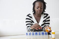 Stock Photo of Black woman putting pills in organizer