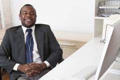 Black businessman listening to music at desk in office - stock photo