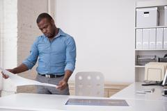 Black architect looking at blueprints in office Stock Photos