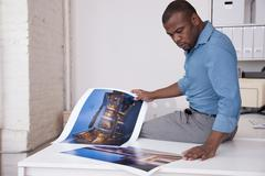 Black businessman looking at photographs in office Stock Photos