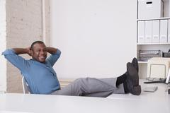 Black businessman sitting at desk with feet up - stock photo