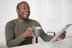 Black man drinking coffee and using digital tablet Stock Photos