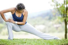 Hispanic woman stretching in grass Stock Photos