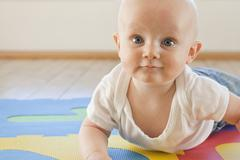 Caucasian baby crawling on plastic mat Stock Photos