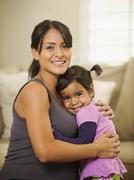Pregnant Hispanic mother hugging daughter Stock Photos