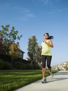 Pregnant Hispanic woman jogging in park Stock Photos