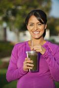 Pregnant Hispanic woman having health drink Stock Photos