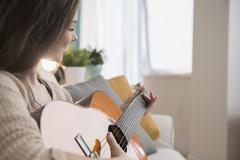 Hispanic girl playing guitar on sofa Stock Photos
