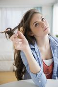 Hispanic girl twirling her hair - stock photo