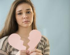 Hispanic girl holding broken heart shape Stock Photos