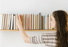 Stock Photo of Hispanic girl selecting book from shelf