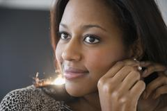 African American woman putting on earrings Stock Photos