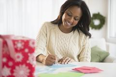 African American woman writing at desk Stock Photos