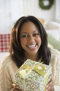 African American woman holding Christmas present - stock photo