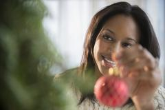 African American woman decorating Christmas tree Stock Photos