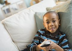 Stock Photo of African American boy watching television on sofa