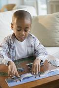 African American boy playing with jigsaw puzzle Stock Photos