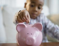 Stock Photo of African American boy putting coins in piggy bank