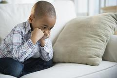 Stock Photo of Sulking African American boy sitting on sofa