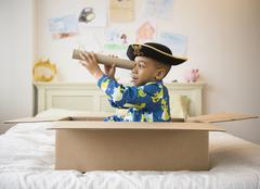 African American boy playing in cardboard box Stock Photos