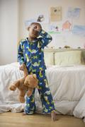 African American boy waking up in bedroom Stock Photos