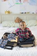 African American boy sitting in suitcase on bed Stock Photos