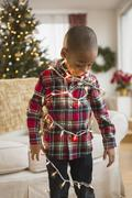 African American boy wrapped in Christmas lights - stock photo