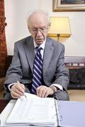 senior businessman going over budget. - stock photo
