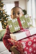African American boy carrying Christmas presents Stock Photos