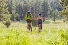 Couple riding mountain bikes in meadow - stock photo