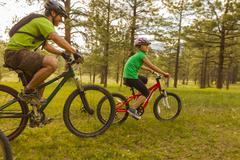 Family riding mountain bikes in meadow Stock Photos