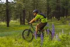 Hispanic man riding mountain bike in meadow - stock photo