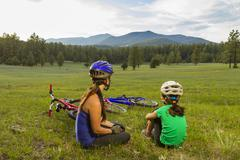 Mother and daughter sitting in meadow Stock Photos