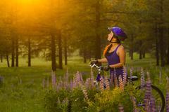 Chinese woman pushing mountain bike in meadow - stock photo