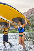 Hispanic couples carrying paddle boards in water Stock Photos