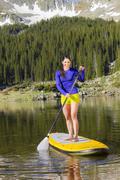 Hispanic woman riding paddle board - stock photo