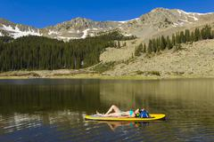 Stock Photo of Hispanic woman laying on paddle board