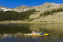 Hispanic woman laying on paddle board Stock Photos