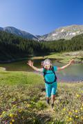 Hispanic hiker walking in rural landscape - stock photo