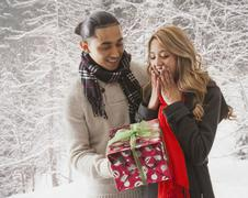 Man giving girlfriend gift in snow - stock photo