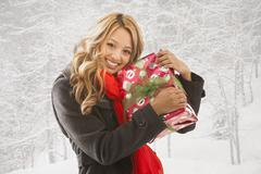 Mixed race woman hugging present in snow - stock photo