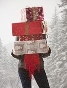 Stock Photo of Mixed race woman holding stack of presents in snow