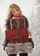 Mixed race woman holding stack of presents in snow Stock Photos