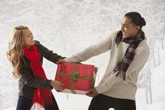 Couple fighting over present in snow - stock photo
