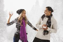 Couple having snowball fight outdoors Stock Photos