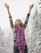 Mixed race woman playing in snow Stock Photos