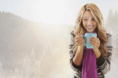 Mixed race woman drinking coffee in snow - stock photo