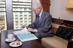 senior businessman going over papers - stock photo
